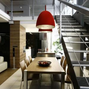 By lampy mogły wisieć przez całą wysokość antresoli, należało przedłużyć ich kabel. Na pożądanej wysokości równoważą dynamiczną kompozycję industrialnych, ażurowych schodów. Stół i krzesła marki Duka. lampy nad stołem Sompex. Fot. Marcin Onufryjuk.