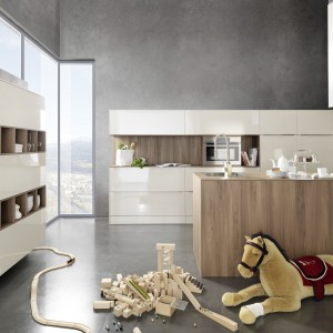 Elegancka kuchnia z kolekcji Puro, w której białe fronty w wysokim połysku zestawiono z laminatem w jasnym, naturalnym kolorze. Takie połączenie tworzy ciepłą, domową atmosferę. Na środku znajduje się wyspa, natomiast na jednej ścianie mamy częściowo otwarte, częściowo zamknięte szafki wiszące, które stanowią bardzo płynne przejście z kuchni do salonu. Wycena indywidualna, Rational.