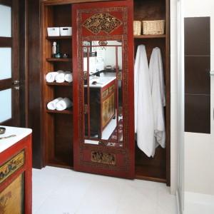 Pojemna wnękowa szafa ze zdobieniami (przerobiona z wielkiego lustra) i duża szafka pod umywalką to orientalne akcenty w nowoczesnej łazience. Oba style, mimo że tak różne, wzajemnie się uzupełniają. Fot. Bartosz Jarosz.