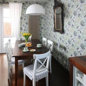 Do masywnego drewnianego stołu, będąca miejscem wspólnych rodzinnych posiłków, dobrano lżejsze w formie krzesła w białym kolorze. Fot. Bartosz Jarosz.