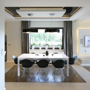 Duży, rodzinny stół został ustawiony pomiędzy salonem a kuchnią. Dzieli on obie przestrzenie, a jednocześnie do spółki z wysokim, ceglanym barkiem, lekko osłania kuchnię przed strefą wypoczynkową. Do stołu wykonanego z białego Corianu dobrano plastikowe, kultowe już krzesła zaprojektowane przez Ray'a i Charles'a Eamsów marki Vitra. Projekt: Agnieszka Hajdas-Obajtek. Fot. Bartosz Jarosz.