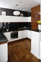 Fronty mebli kuchennych wykonane są z płyty mdf lakierowanej na wysoki połysk, blaty z granitu, a ścianę nad nimi pokrywa niezwykle efektowna tafla czarnego szkła. Fot. Bartosz Jarosz.