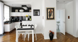 Autor projektu wnętrza – arch. Iwo Kęsy, zaproponował zestawienie bieli zabudowy z czernią blatu i ściany oraz ocieplenie nowoczesnej, chłodnej aranżacji za pomocą forniru palisandru. Z fornirowanej płyty wykonany został cokół oraz część
