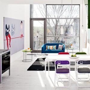 Wnętrze jest jasne i pełne światła, dzięki czemu loft wydaje się dużo większy niż w rzeczywistości. Taka przestrzeń pozwoliła także wyeksponować duże, kolorowe obrazy w salonie (Galeria Napiórkowskiej, Warszawa).