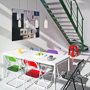 Każde krzesło w jadalni jest w innym kolorze, a jednak wszystko do siebie doskonale pasuje. Takie zestawienie prezentuje się wyjątkowo oryginalnie. Stół to propozycja firmy IKEA, krzesła wybrano z oferty Seletti.