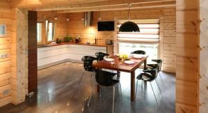 Drewniane ściany z bali i białe, nowoczesne meble na wysoki połysk. Niemożliwe? A jednak. W tej kuchni stworzyły naprawdę niezwykły klimat.