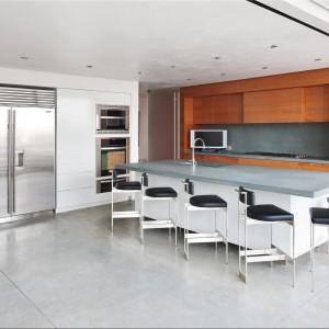 Nowoczesna kuchnia z prostą drewnianą zabudową kuchenna w minimalistyczny, nieco industrialnym klimacie. Fot. Douglas Elliman Real Estate.