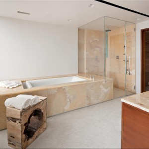 Jedna ze znajdujących się w apartamencie łazienek. Uwagę zwraca kamień na obudowie wanny, prysznica i łazienkowym blacie. Fot. Douglas Elliman Real Estate.