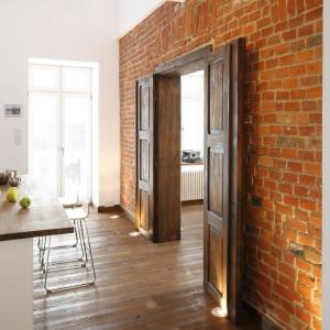 Odkryte ceglane surowe mury i zachowane w oryginale podwójne drzwi  to ukłon architekta w stronę historii tego domu.  Fot. Bartosz Jarosz.