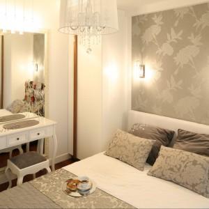 Delikatne oświetlenie nad łóżkiem nawiązuje formą do pozostałego oświetlenia utrzymanego w stylu glamour. Proj.Małgorzata Mazur. Fot.Bartosz Jarosz.