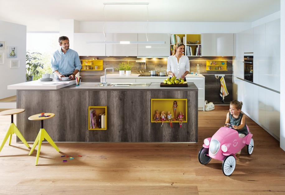 Nowoczesna zabudowa kuchenna Fino, w której spokojne, stonowane fronty w wysokim połysku ożywia kolor żółty dodający wnętrzu pozytywnej energii. Całość spina dębowy blat (Dąb Havana Brown NB). Wycena indywidualna, Schüller.