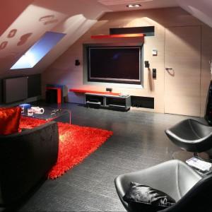Zaprezentowane pomieszczenie to świątynia kinomaniaków. Połączenie ciepłej kolorystyki ze skórzaną podłogą i szarością ściany pięknie dopełniają ciemne meble i akcenty w postaci krwisto – czerwonych poduch i dywanu. Fot. Bartosz Jarosz.