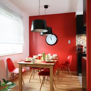 Do dużego, dębowego stołu (Duka) o jasnej, ciepłej barwie dobrano delikatne krzesła w żywym, czerwonym kolorze marki Vitra. Lampy nad stołem to IKEA. Projekt: Dorota Szafrańska. Fot. Bartosz Jarosz.