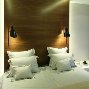 Czarne kinkiety umieszczone w ścianie stanowią ciekawy akcent. Białe stoliki nocne nie konkurują z dekoracyjną ścianą. Proj.Nasciturus Design. Fot.Bartosz Jarosz.