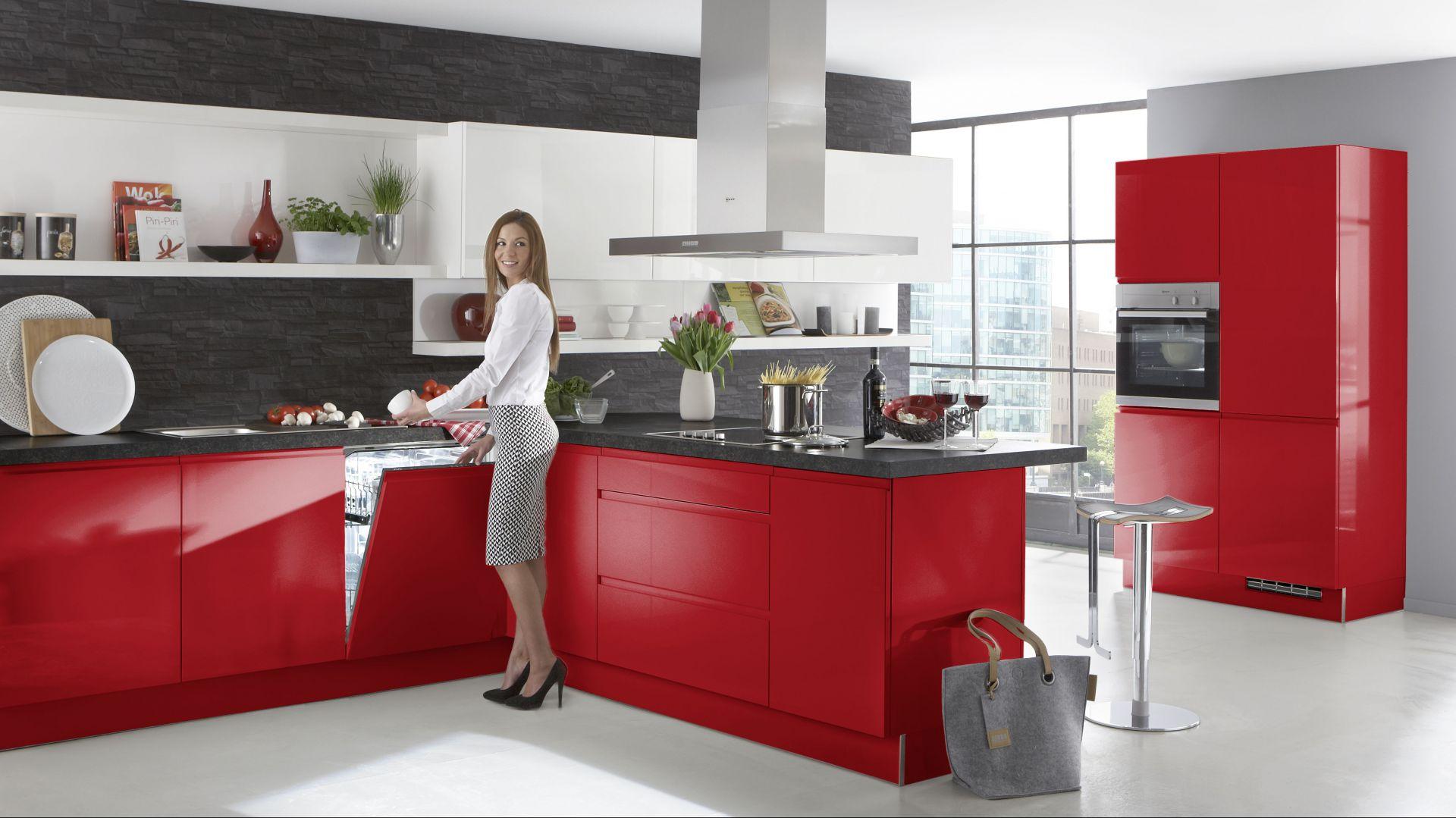 Nowoczesne meble kuchenne Alpha Lack 55R zfrontami wykończonymi wwysokim połysku. Intensywna czerwień doskonale kontrastuje z bielą górnej zabudowy i kolorem szarym zastosowanym na ścianach. Szafki otwierają się bezuchytowo. Wycena indywidualna, Nolte Küechen.