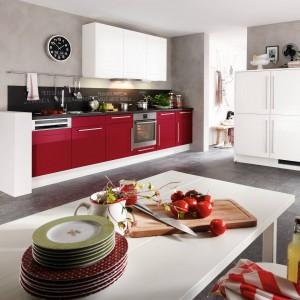 Kuchnia z programu PN 475. Dolne szafki w kolorze czerwonym zestawione zostały z ciemnym, szarym blatem oraz z górną zabudową w spokojnym, białym kolorze. Duże, wygodne uchwyty doskonale spinają całość. Wycena indywidualna, Pino.