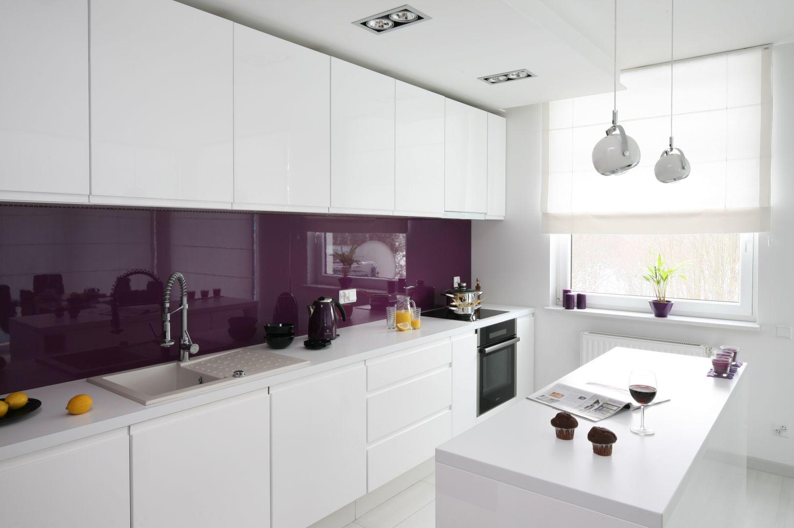 Zabudowa kuchenna wykonana została z lakierowanego MDF-u w dwóch kolorach: białym i fioletowym. Typowe uchwyty zastąpiły tu podfrezowania we frontach. Fot. Bartosz Jarosz.