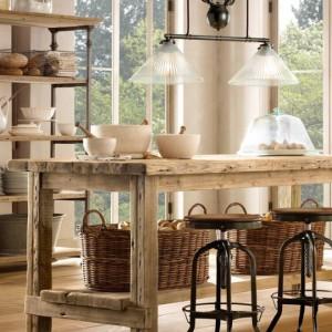 Lamy wiszące doświetlają drewniany stół, pełniący różnież (jeśli trzeba) funkcję kuchennej wyspy.Fot. Rastoration Hardware/SquareSpace.