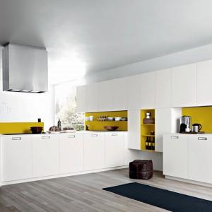Meble kuchenne Kora w kolorze białym. Żółty zastosowany został tu w dodatkach: na ścianie i na fragmencie wyspy. Szafki górne otwierane są bezuchytowo. Blaty wykonane z Corianu. Wycena indywidualna, Cesar.