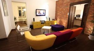 Salon w starym domu zaaranżowano w eklektycznym stylu łącząc pozostałą po rewitalizacji czerwoną cegłę z nowoczesnym wyposażeniem- kolorowąsofączy komodą. Zobaczcie ciekawą aranżację wnętrza.