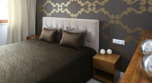 Główną rolę w sypialni gra brązowa tapeta ze złotym ornamentem. W połączeniu z jasnymi odcieniami tworzy wyjątkowo przytulne wnętrze.