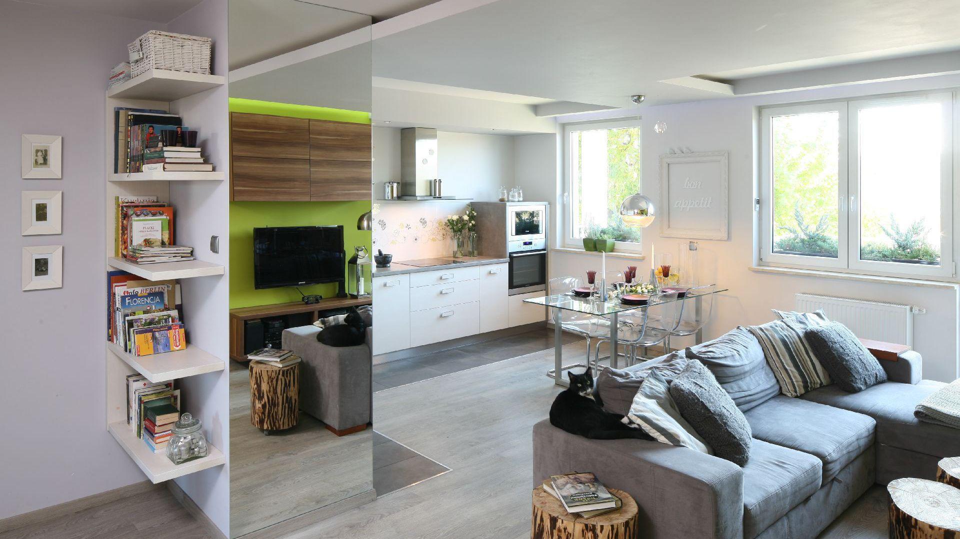 Ciemnoszara, ciężka kanapa jest najmocniejszym elementem wyposażenia salonu. Fot. Bartosz Jarosz.