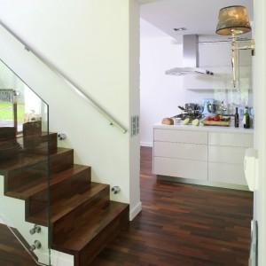 Drewno egzotyczne Lapacho pojawia się w salonie, ale i na schodach. Dodatkowo podkreśla je szklana balustrada, w której odbija się zieleń ogrodu. Fot. Bartosz Jarosz.