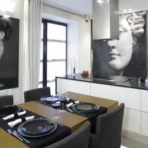 Elegancka zabudowa kuchenna w lśniącym, białym kolorze zestawiona została z czarnym blatem. Projekt: Julita Chrząstek. Fot. Bartosz Jarosz.