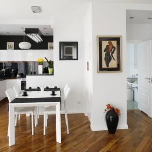 Meble kuchenne wykonano z białego, lakierowanego MDF-u. W kolorze czarnym jest kamienny blat oraz ściana, którą pomiędzy szafkami zabezpieczano szkłem. Zestaw bieli i czerni ociepla drewno teakowe. Projekt: Iwo Kęsy. Fot. Bartosz Jarosz.