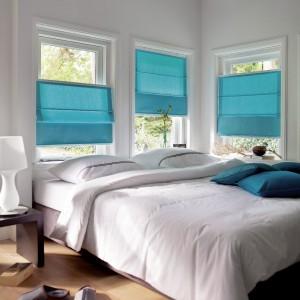 Niebieska rolety marki Gardinia dobrze wyglądają w białej sypialni. Fot. Gardinia.