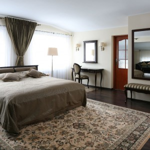 W sypialni dominują przytulne beże i brązy, za zasłonami znajdziemy dodatkowe miejsce wypoczynkowe. Fot. Bartosz Jarosz.