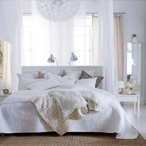 Białe ściany w połączeniu z jasnymi tkaninami tworzą przytulną, przestronną sypialnię.Fot.Ikea.