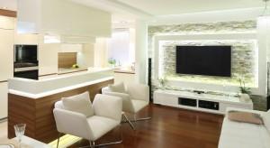 Kuchnia znajduje się otwartej strefie dziennej. Ponadczasowy, elegancki charakter wspólnej przestrzeni nadaje duet bieli i drewna.