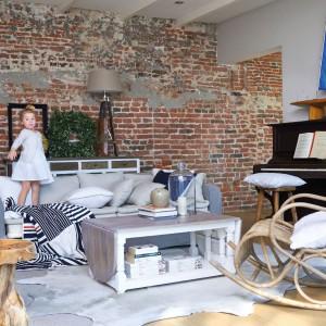 Jak dobrać meble i dodatki do ściany z cegły? Sprawdzą się naturalne materiały i wyposażenie w surowym loftowym stylu, choć na tle cegły pięknie wyglądać także będą meble i dekoracje w stylu vintage. Na zdjęciu fotel bujany Hennessy z rattanu – 2.165 zł, stołek z litego drewna Amazone - 615 zł, stolik kawowy Morningside – 4.903 zł, sofa Origins – 13.426 zł, kapa w biało-niebieskie pasy z kolekcji Breton – 1.028 zł. Riviera Maison/HOUSE&more.