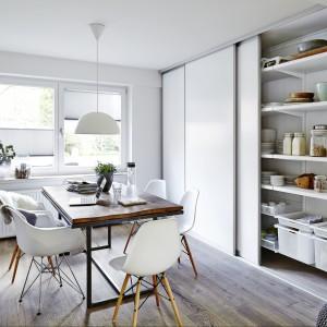 Poziome półki zajmują całą ścianę, dzięki czemu zapewniają sporo miejsca na przechowywanie. Zaplanowano je tak, że wszystkie umieszczone na nich przedmioty są doskonale widoczne. Całość chowają przesuwne drzwi w białym kolorze idealnie dopasowane do aranżacji wnętrza. Wycena indywidualna, Elfa.