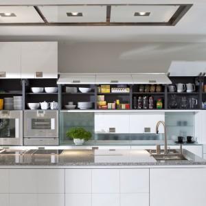 Kuchenna zabudowa została bardzo funkcjonalnie zorganizowana. Liczne szafki i półki zapewniają naprawdę sporą powierzchnię przechowywania, a fronty wykończone białym lakierem nadają całości elegancki charakter. Na zdjęciu: meble kuchenne Torino firmy Mebel Rust.