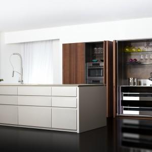 Wysoka zabudowa skrywa sprzęt AGD (piekarnik, mikrofalówka) oraz zapewnia sporo miejsca na przechowywanie kuchennych akcesoriów. Jej fronty w brązowym kolorze ładnie łącza się z bielą zastosowaną na wyspie. Na zdjęciu: meble kuchenne firmy Toncelli.