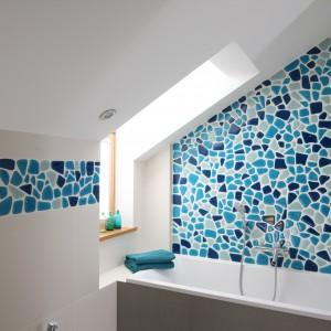Głównym motywem dekoracyjnym w tej łazience jest mozaika w różnych odcieniach koloru niebieskiego – od bardzo jasnego do nieco ciemniejszego. Zdobi całą ścianą przy wannie (Villeroy&Boch) oraz fragmenty w pozostałej części wnętrza. Projekt: Małgorzata Galewska. Fot. Bartosz Jarosz.