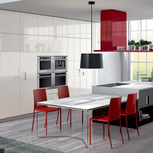 Meble z kolekcji Carré. Białe, lśniące fronty połączone z elementami w kolorze czarnym nadają kuchni elegancki klimat, natomiast czerwone dodatki ładnie ożywiają przestrzeń. Wycena indywidualna, Ernestomeda.