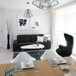 Dzięki wszechobecnej bieli można pozwolić sobie na silny akcent w postaci kolorystyki kanapy i fotela. Fot. Bartosz Jarosz.