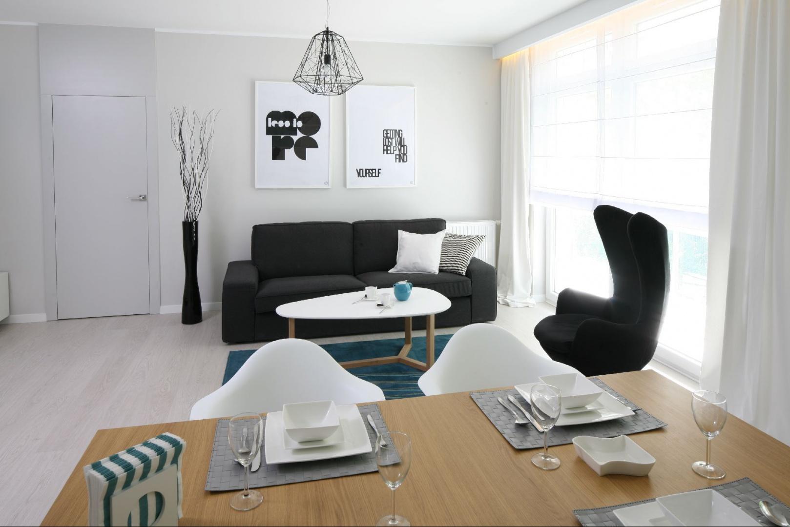 Salon płynnie łączy się z jadalnią. Duże okno wpuszcza światło i przestrzeń. Fot. Bartosz Jarosz.