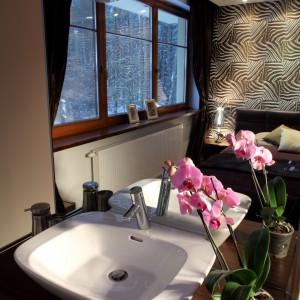 Otwarta przestrzeń sypialni została dodatkowo powiększona przez bardzo duże lustro przy umywalce. Projekt Katarzyna Moraczewska. Fot. Tomasz Markowski.