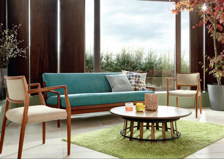 Zielona sofa i dywan imitujący trawę komponują się z drewnianymi elementami. Fot. Mark Alexander.