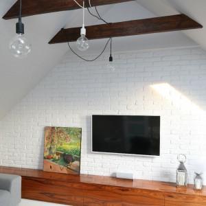 Ścianę szczytową wyłożono postarzanymi płytkami ceglanymi, które pomalowano na biało. Poprzez zastosowanie jasnej kolorystyki ścian i sufitu wyeksponowano jętki będące elementami konstrukcyjnymi więźby dachowej. Fot. Bartosz Jarosz.