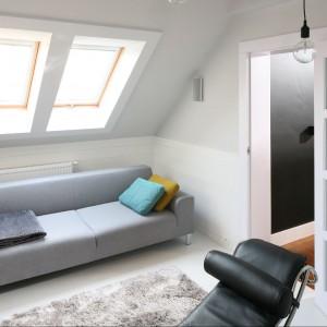Do wysokości ściany kolankowej zamontowano tzw. lamperię wykonaną z podbitki dachowej pomalowanej na biało. Wyposażenie: sofa ModAlto / drzwi wykonane według projektu Tissu. Fot. Bartosz Jarosz.