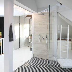Kabina wyposażona została w podtynkową baterię prysznicową. Płytki, na ścianie z instalacją, ułożono naprzemiennie, nawiązując do sposobu montowania cegieł, których motyw powtarza się w sąsiednich pomieszczeniach. Fot. Bartosz Jarosz.