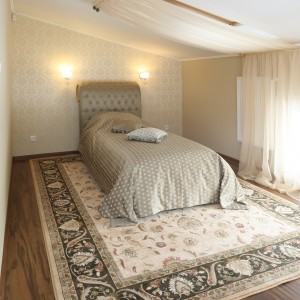 Poza głównym łóżkiem znajduje się tu drugie, jednoosobowe usytuowane na jednym z końców pomieszczenia w kształcie litery U. Projekt Małgorzata Goś. Fot. Bartosz Jarosz