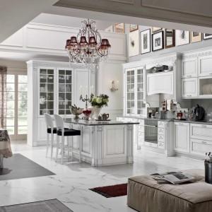 Meble kuchenne z kolekcji Dolcevita w salonowym stylu. Eleganckie i pełne uroku. Wszystkie, nawet najdrobniejsze elementy, zostały dokładnie przemyślane i dobrane. Zdobione fronty w białym kolorze pięknie prezentują się w połączeniu z podłogą wykończoną marmurem. Meble wykonane są z drewna. Wycena indywidualna, Stosa Cucine.