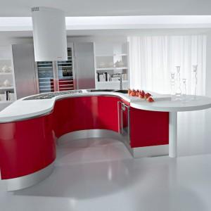 Meble kuchenne z kolekcji Artika. Wyspa mimo nietypowej formy jest w pełni funkcjonalna. Stanowi centrum wszelkich kuchennych prac. Kolor czerwony, którym wykończone zostały fronty wyspy ożywia białe wnętrze. Wycena indywidualna, Pedini.