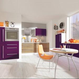 Meble kuchenne z programu PN 230. Mocny fiolet, zastosowany tu w odpowiednich proporcjach, ładnie łączy się z równie mocnym kolorem pomarańczowym i z nieco spokojniejszą tonacją na ścianach i dolnych szafkach. Wycena indywidualna, Pino.